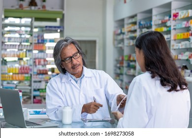 Professional Asian senior male pharmacist prepare prescription medicine capsule or supplementary food to female patient in hospital pharmacy drugstore. Medical, pharmaceutical and healthcare concept.