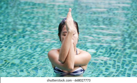 professional asian woman practice yoga sequence eagle pose (Garudasana) close up in swimming pool, aqua yoga blue water