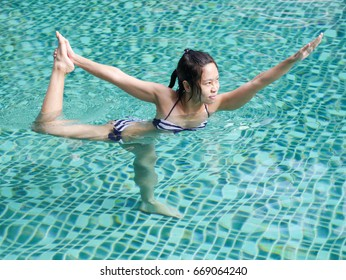 professional asian woman practice yoga sequence standing bow pulling pose close up in swimming pool, aqua yoga blue water