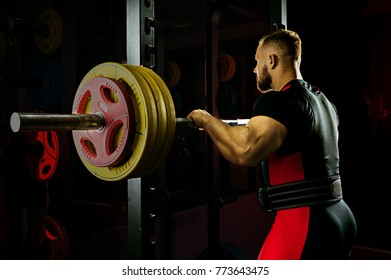 Professional athlete prepares to squat with a barbell. Mixed media