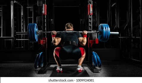 Professional athlete sits with a barbell on his shoulders and prepares to stand with her. View from the back.