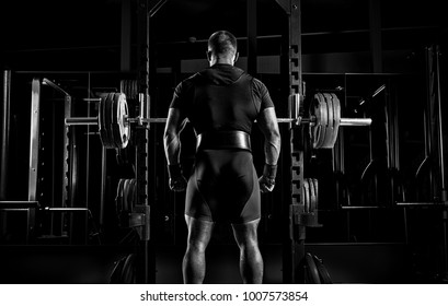 Professional athlete stands in front of the bars with a barbell and is about to crouch with her. Back view