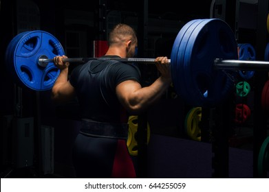 Professional athlete stands in the gym with a barbell on his shoulders