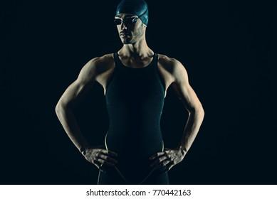 Professional athlete swimmer studio portrait against black background. Blue tone color correction.