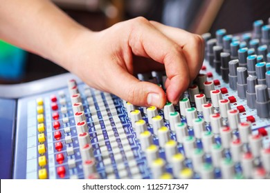 Professional audio engineer adjusting mixing concole.