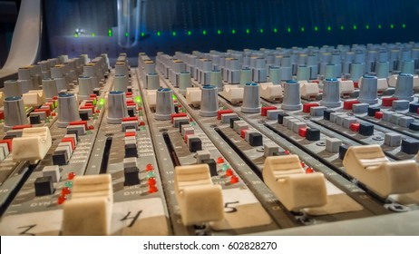 Professional audio mixing console with faders in recording studio.