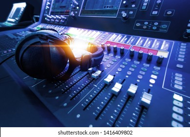 Professional audio studio sound mixer console board panel with recording , faders and adjusting knobs,TV equipment. Blue tone and close-up image with flare light effect. - Shutterstock ID 1416409802