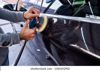 Professional auto detailer hand holding air random orbital sander or dual action polisher while waxing paint surface of shiny black sedan. Car detailing, car wash, and paint sealant concept.