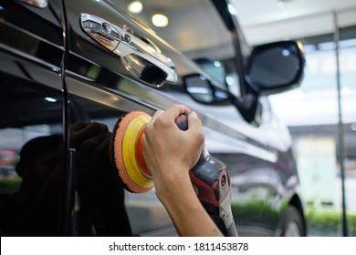 Professional auto detailer hand holding rotary polisher while polishing paint surface of shiny black sedan. Car detailing, car wash, and paint correction concept. Random orbital polisher background.