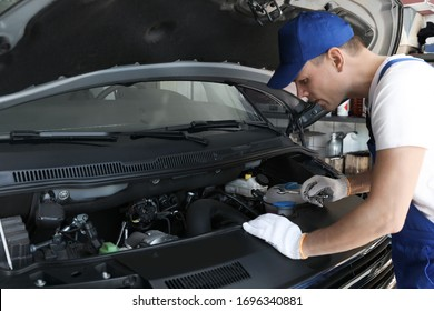 Professional auto mechanic fixing modern car in service center