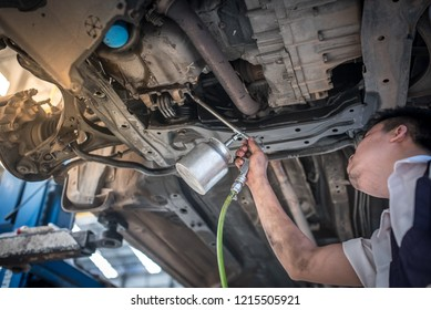 Professional auto mechanic working on the undercarriage of a car diligence attention inspection examination annual checkup safety insurance professionalism occupation transportation vehicle concept