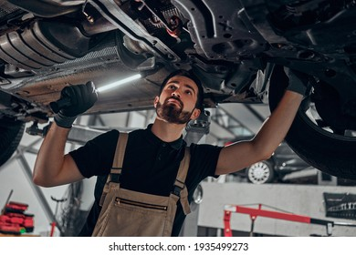 Professional auto mechanic working on the undercarriage of a car. Diligence, attention, inspection, examination, annual checkup, safety, insurance, professionalism, vehicle concept. Bottom view.