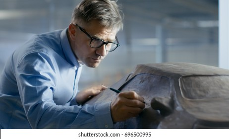 Professional Automotive Designer with Rake Sculpts Futuristic  Car Model from Plasticine Clay. He Works in a Special Studio Located In a Large Car Factory.