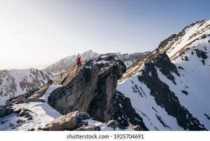 A professional backcountry skier with a backpack and skis stands on a rock in the mountains. Concept: Hike, Freedom, Explore, Journey. Enjoying idyllic view of mountain range.