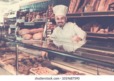 Professional baker is demonstrating assortment of bakery.