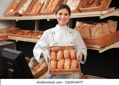 Professional baker holding tray with fresh buns in store