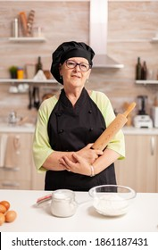 Professional baker smiling at camera in home kitchen wearing apron and bonete. Retired elderly baker in kitchen uniform preparing pastry ingredients on wooden table ready to cook homemade tasty bread,