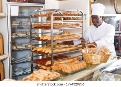 Professional baker working behind counter in bakeshop, pushing steel trolley with baked baguettes