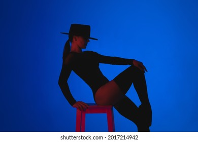 Professional ballet dancer in hat sitting on high chair on multi-colored background under violet neon light. Sensual sexy ballerina dancing with her legs in stockings. Femme fatale outfit.High quality