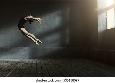 Professional ballet dancer performing in the dark lighted room