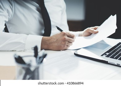 Professional banker working at his office with documents and using modern laptop computer, close-up of male hands signing contract