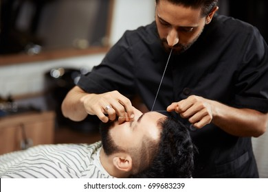 Professional barber doing eyebrow threading for male client in chair.