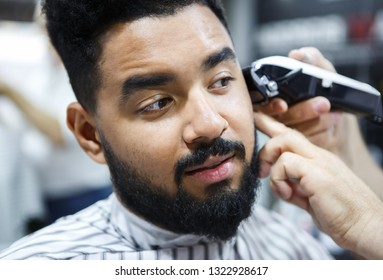 Professional barber makes new haircut with electric shaving machine.Young black man recevie new haircut in barbershop.Male beauty treatment in close up.Pro hairdresser tools in beauty salon