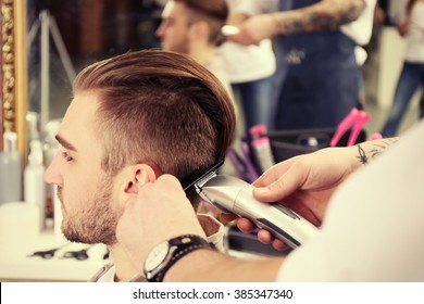 Professional barber making stylish man haircut