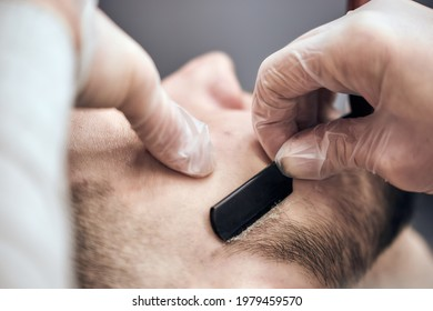 Professional barber shaves beard to young man using straight razor at the barbershop. Close-up, selective focus
