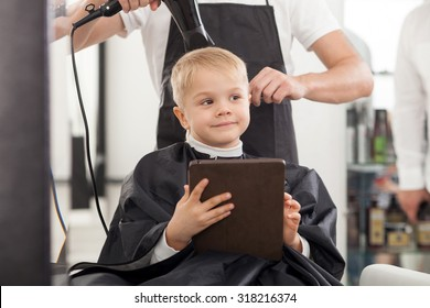 Professional barber is standing and drying hair of boy. The child is sitting in chair and smiling. He is holding a tablet and dreaming