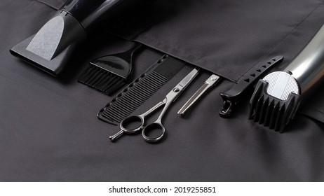 Professional barber tools, in the pocket, black stylist apron, horizontal, no people,