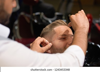 Professional barber in white shirt doing threading procedure and correcting shape of eyebrows to young male client sitting in chair in barber shop. Concept of styling and care.