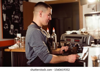 Professional barista holding metal jug warming milk using the coffee machine. Happy young man preparing coffee at counter.