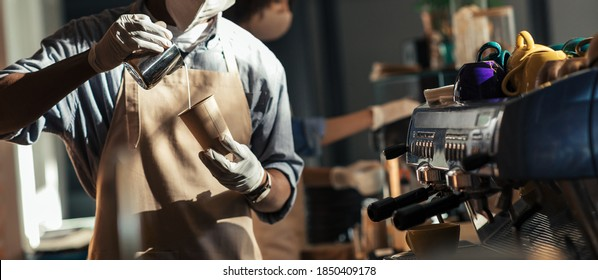 Professional barista makes cappuccino during social distance. African american male hipster in apron, protective gloves and mask, pours milk in takeaway paper cup for client, cropped, panorama