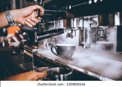 Professional Barista Making Coffee with machine in coffee shop or cafe.