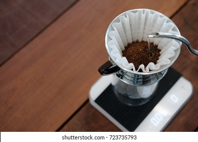 Professional barista pouring hot water on coffee ground with paper filter. Drip coffee or pour-over coffee on the scale with copy space.
