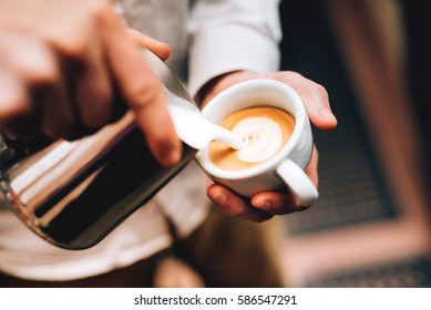 Professional barista pouring latte foame over coffee, espresso and creating a perfect cappuccino