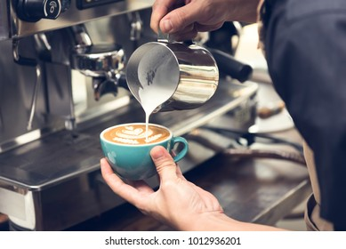 Professional barista pouring steamed milk into coffee cup making beautiful latte art Rosetta pattern