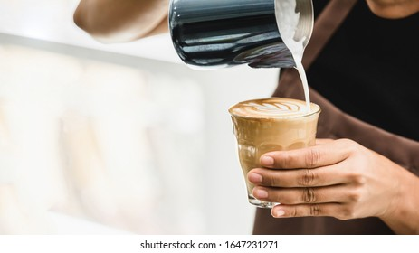 Professional barista pouring steamed milk into coffee glass cup making beautiful latte art Rosetta pattern in cafe