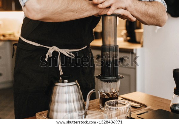 Professional barista preparing coffee in aeropress, alternative coffee brewing method. Hands on aeropress and glass cup, scales, manual grinder, coffee beans, kettle on wooden table