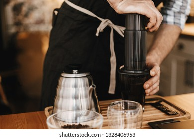 Professional barista preparing coffee by aeropress alternative method, brewing process. Hands on aeropress and glass cup, scales, manual grinder, coffee beans, kettle on wooden table
