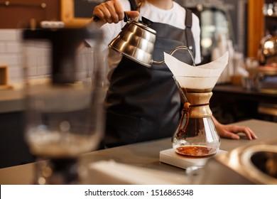 Professionelle Barista, die Kaffee mit Chemex gießen über Kaffeemaschine und Wasserkocher zubereitet. Alternative Formen des Kaffeehandels. Konzept des Kaffeehauses