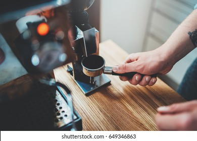 Professional barista preparing fresh espresso, hipster man holding portafilter loaded with grinded coffee and preparing morning cappuccino