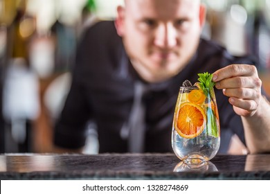 Professional barman decorated gin tonic cocktail drink and decorated it with mint herbs.