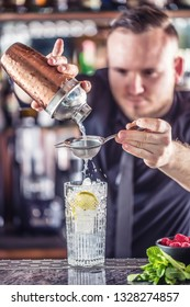 Professional barman making  alcoholic cocktail drink with fruits sugar and herbs.