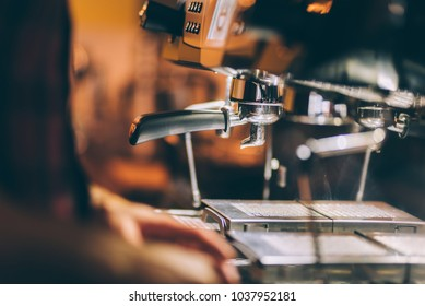 Professional barman preparing fresh espresso with industrial coffee machine in local pub, bistro or restaurant