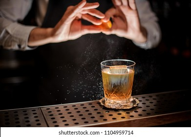 Professional bartender adding juice from a piece of an orange zest to the fresh alcoholic cocktail drink on the bar counter