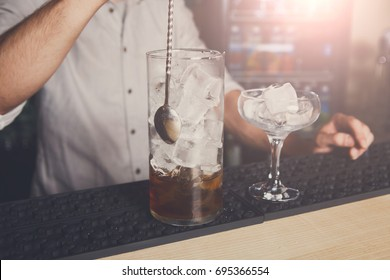 Professional bartender in bar interior mixing cosmopolitan alcohol cocktail, pouring sweet drink into glass