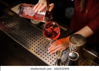 Professional bartender girl pouring a delicious campari cocktail into the glass at the steel bar counter