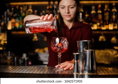 Professional bartender girl pouring a delicious campari red cocktail into the glass at the steel bar counter